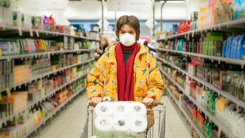 24.03.2020 Russia Saint Petersburg, a young woman in a store in a protective mask selects products