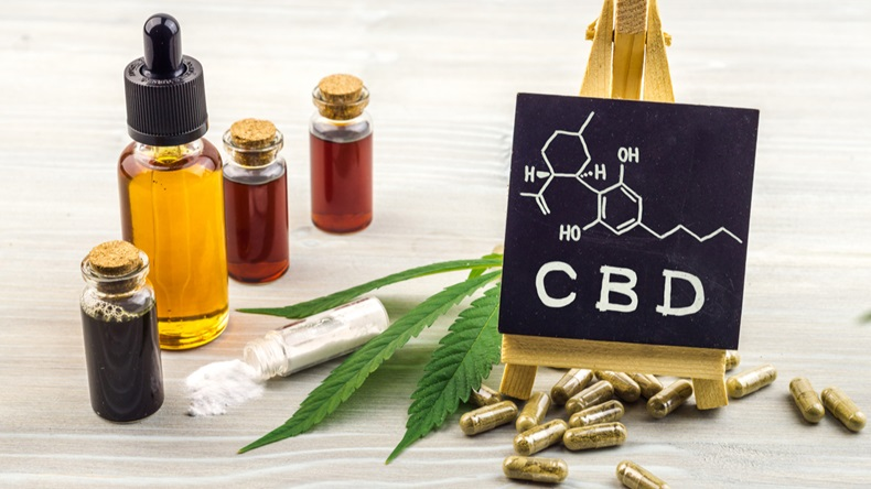 Full spectrum Cannabidiol CBD oils, capsules and crystals isolate with small blackboard with CBD word and chemical structure on wooden backdrop - Image