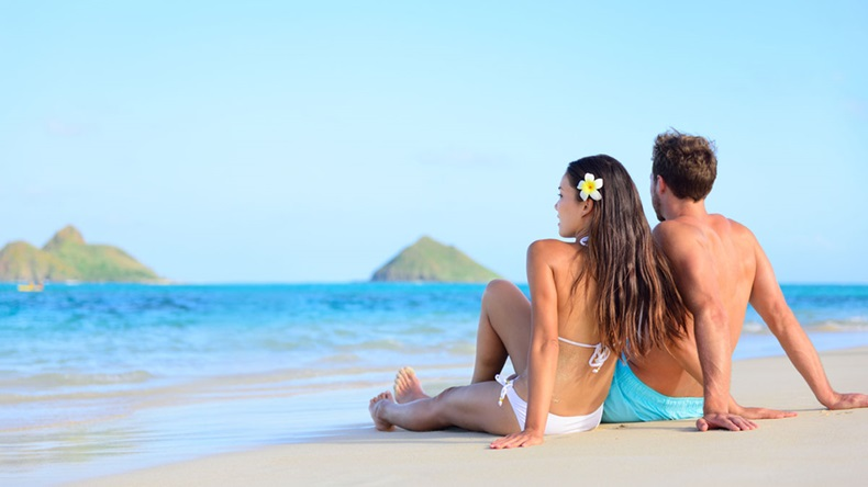 Hawaii vacation couple relaxing tanning on beach. Beautiful young adults in love on hawaiian holidays lying down on white sand of Lanikai beach, Oahu island, Hawaii, USA.