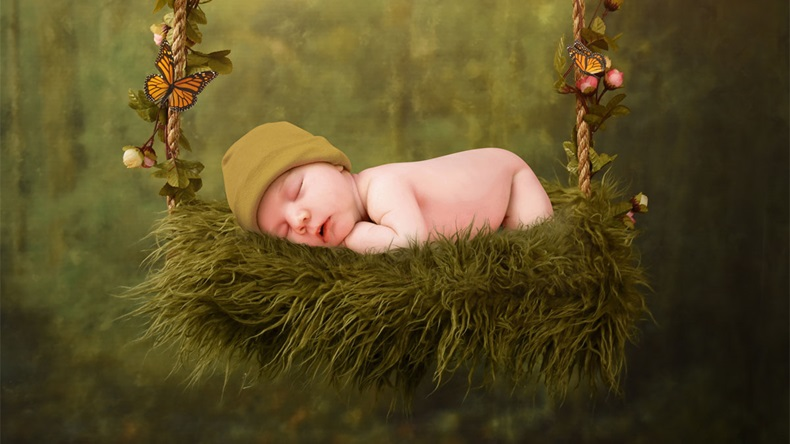 A young newborn baby is sleeping on a flower swing in an enchanted forest for a dream fairy concept.