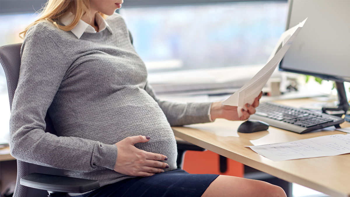 pregnancy, business and work concept - smiling pregnant businesswoman sitting at office table and reading papers