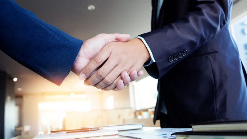 Two businessmen shaking hands during a meeting in the office, success, dealing, greeting & business partner concepts - soft light.