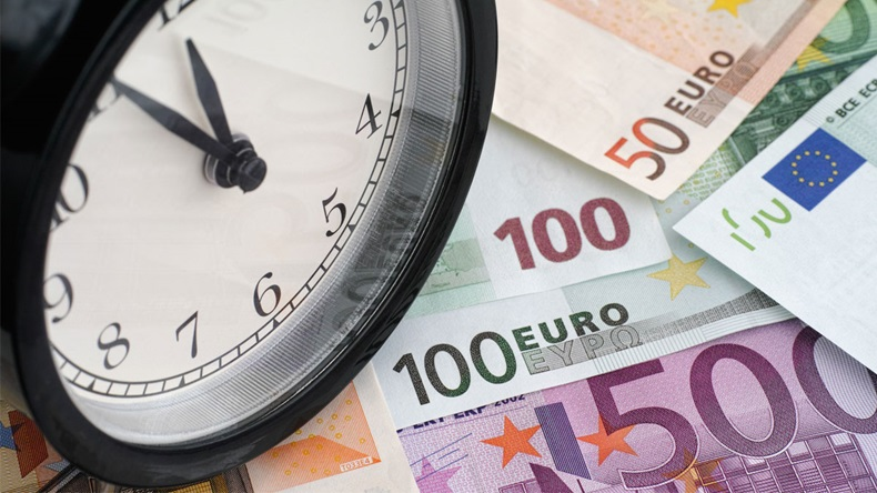 Time is money. Alarm clock and euro banknotes.