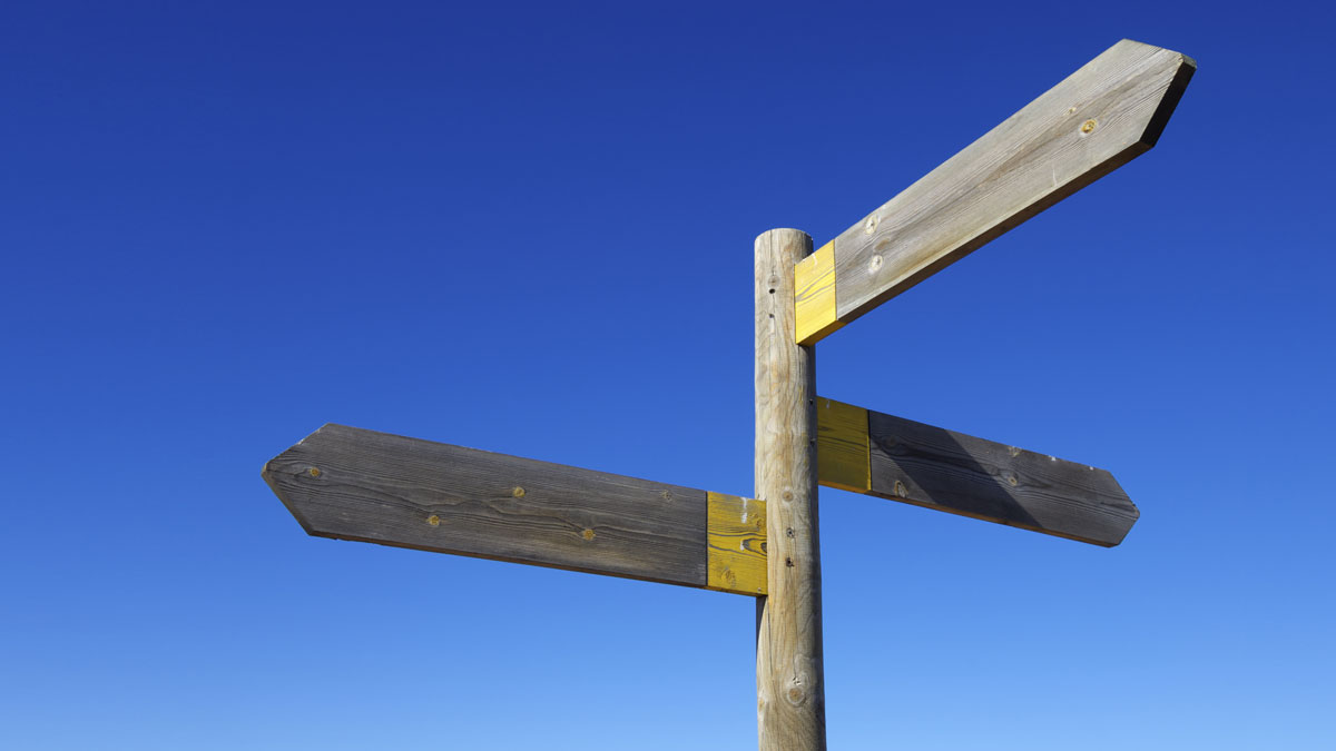 view of three wooden directional signs on a pole - Image