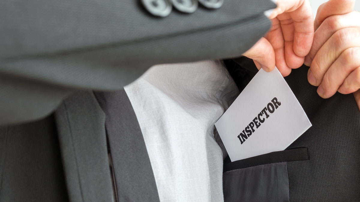 Inspector removing a white card with Inspector sign from the inner pocket of his jacket. Conceptual of health, business or other inspection coming over unannounced.